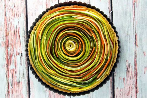 a spiral vegetable tart with concentric circles of zucchini, squash, and carrots in a tart pan