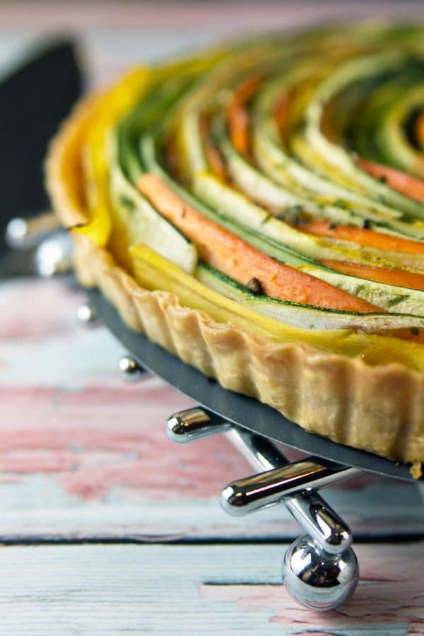 side view of a spiral vegetable tart showing the flaky tart crust with the concentric spirals of thinly sliced vegetables