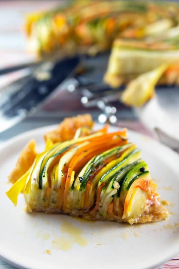 one slice of a spiral vegetable tart on a small appetizer plate showing the slices of vegetables from the side