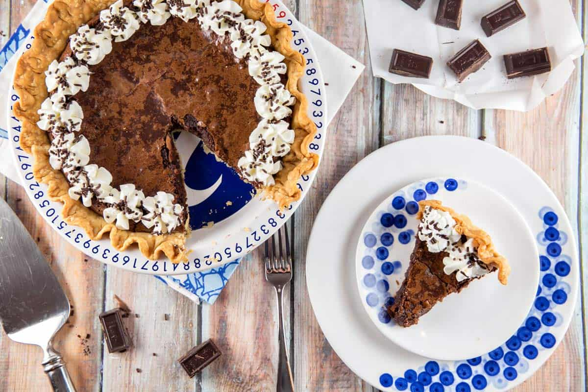 flourless chocolate brownie pie with one slice removed on a blue and white plate