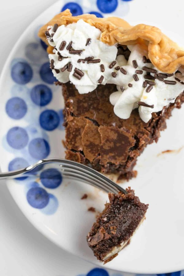 a slice of flourless chocolate brownie pie on a white and blue plate with one forkful removed