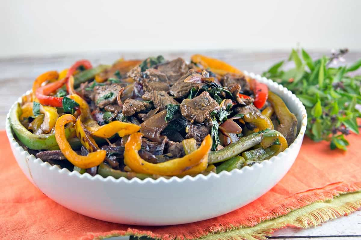 side view of white bowl with thai beef and peppers piled over the top