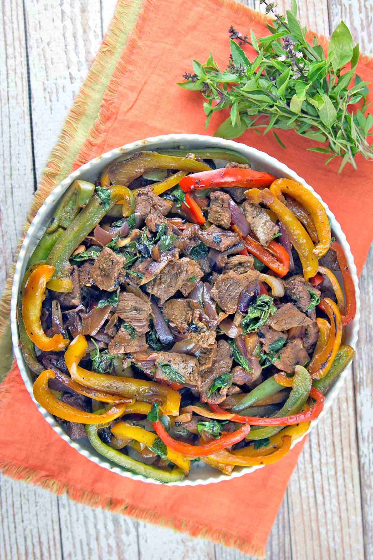 overhead photo of beef, red yellow and green peppers, and thai basil on an orange placemat