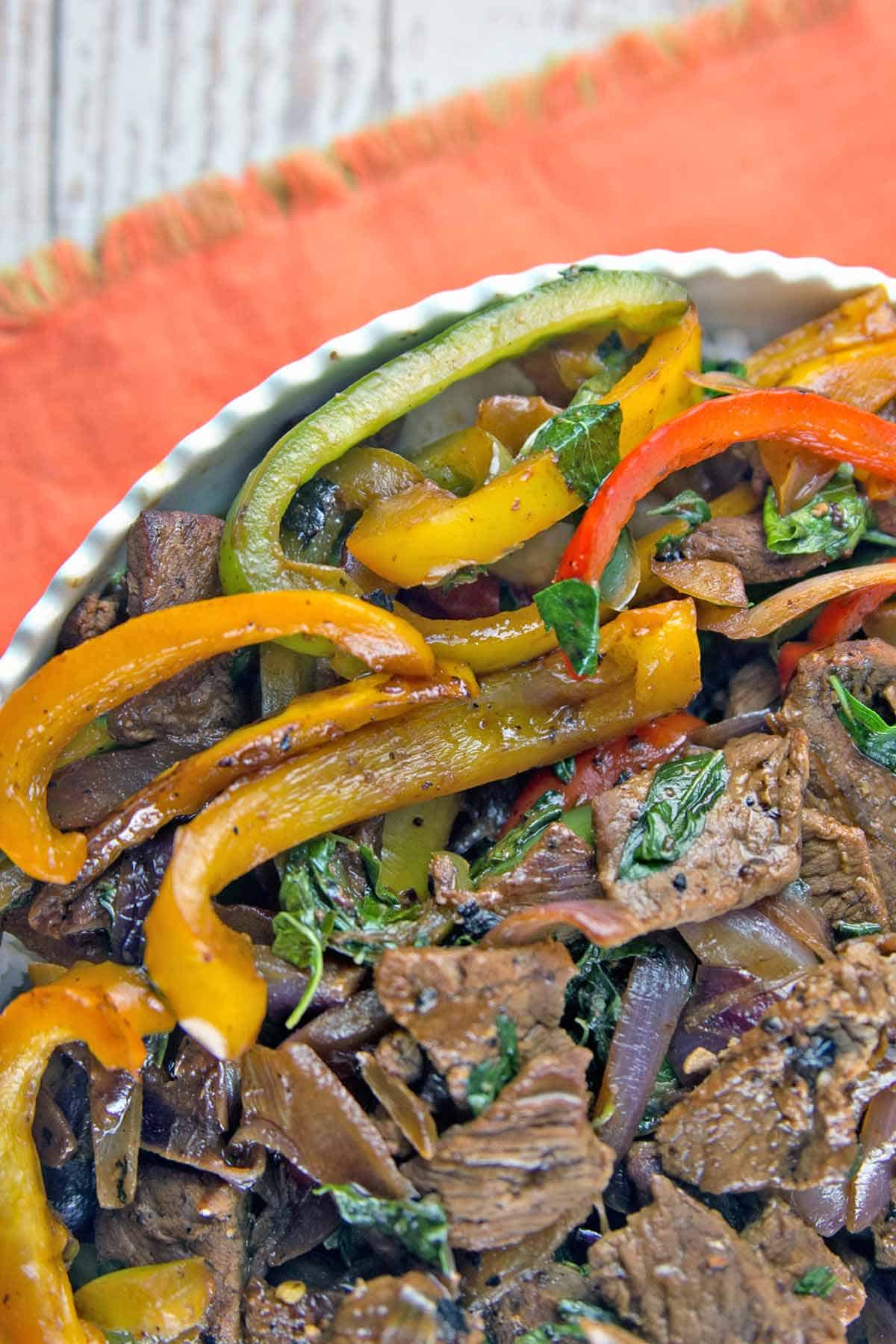 close up photo of browned Thail basil beef with brightly colored bell peppers