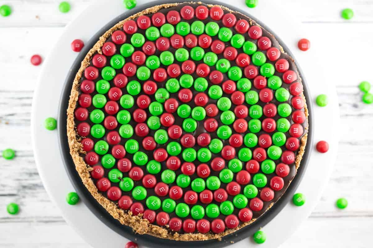 overhead view of a peanut butte pretzel pie covered in concentric circles of m&ms