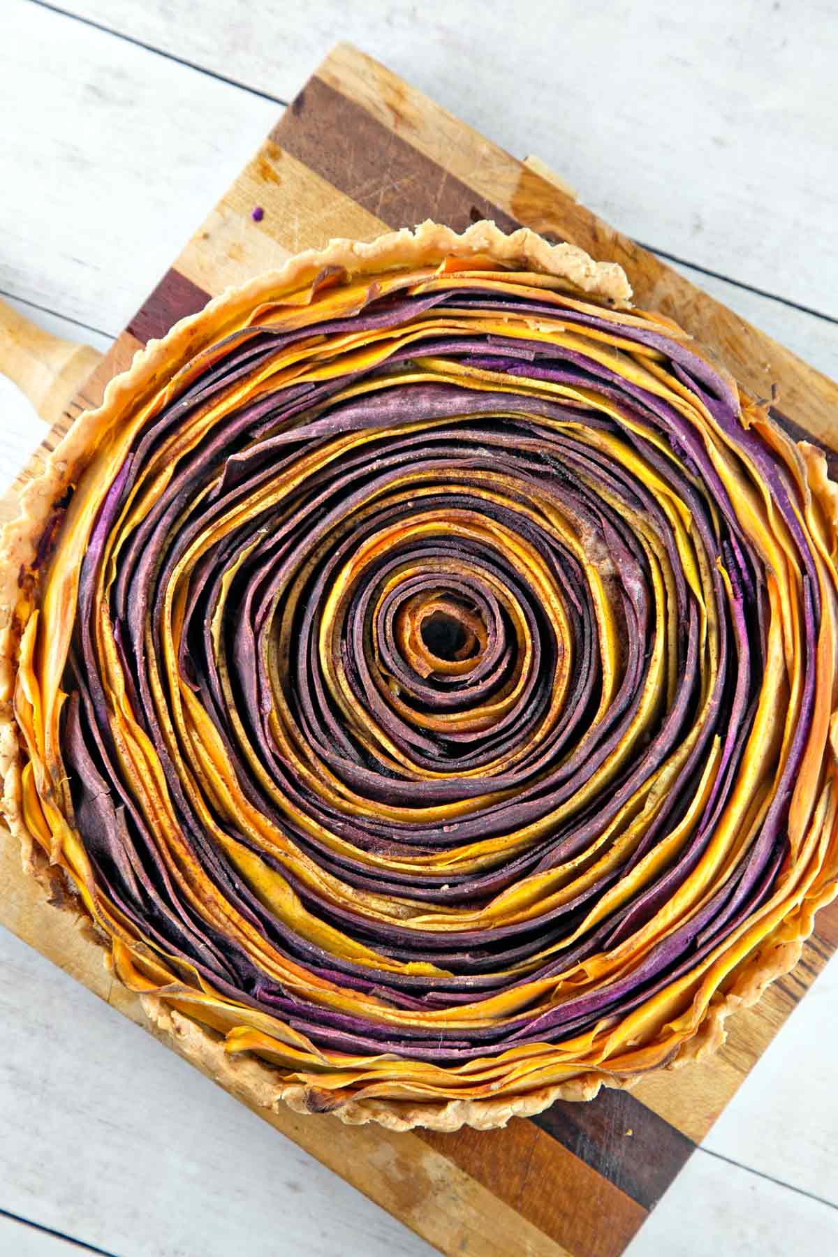 baked sweet potato tart made in a spiral design with circles of orange and purple potatoes