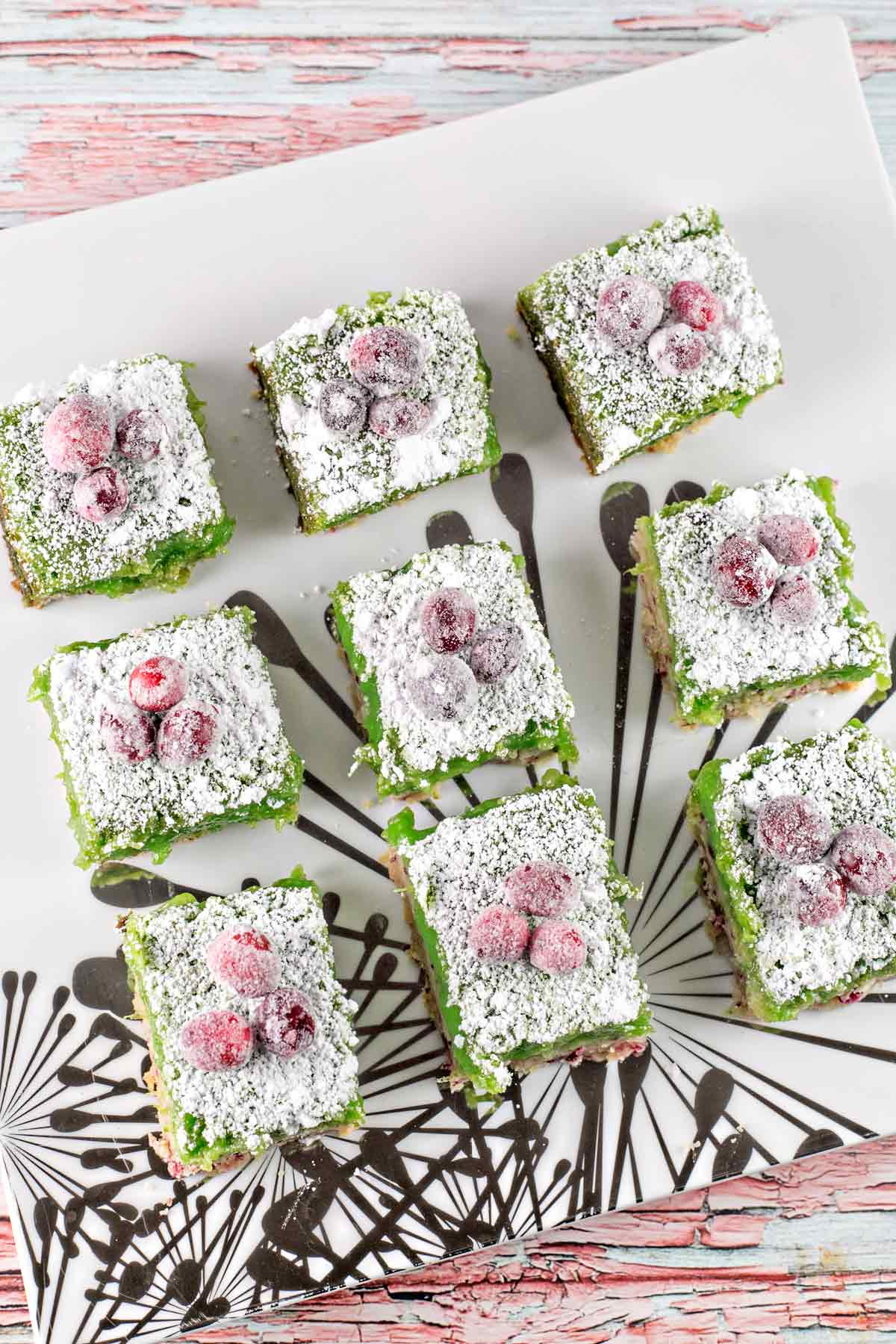 cranberry lime bars topped with sugared cranberries arranged on a serving dish