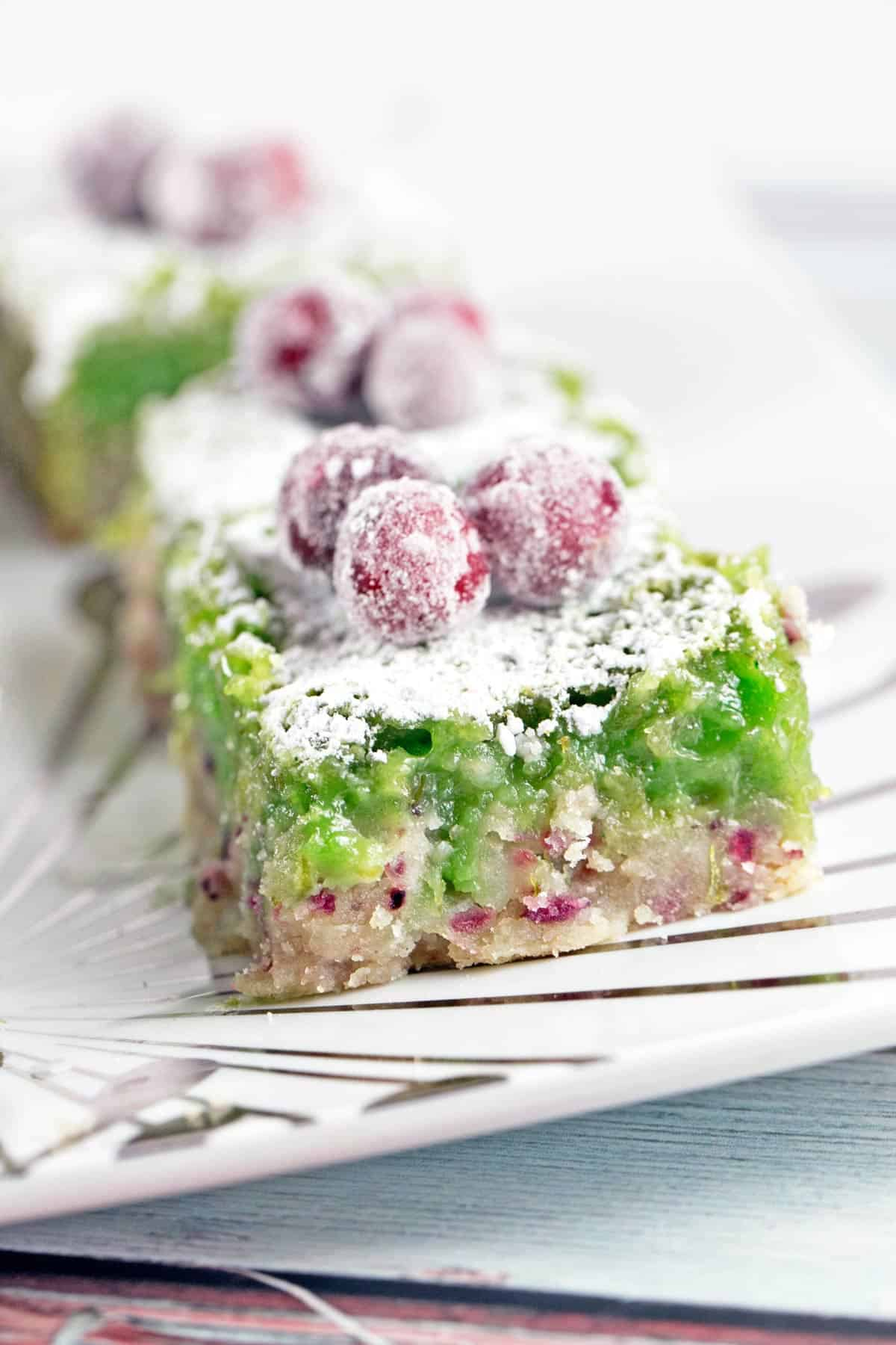 close up view of the side of a cranberry lime bar with green lime filling