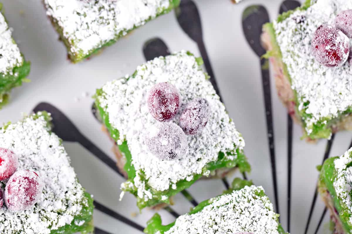 lime bars with cranberry shortbread dusted with powdered sugar and topped with sugared cranberries