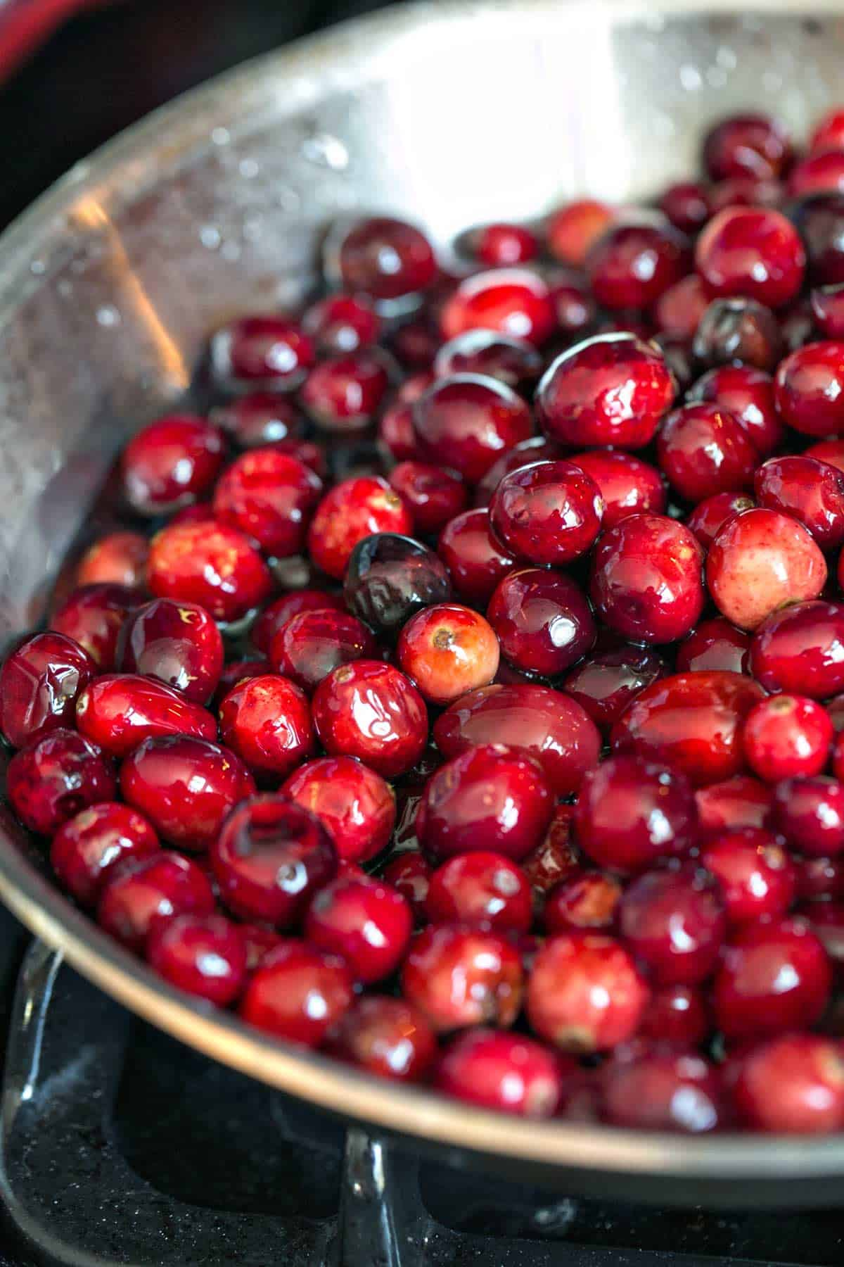 cranberries in a pot on the stove simmering in water