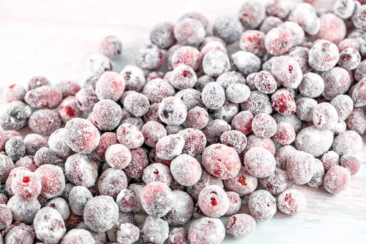 sugared cranberries piled on a piece of parchment paper