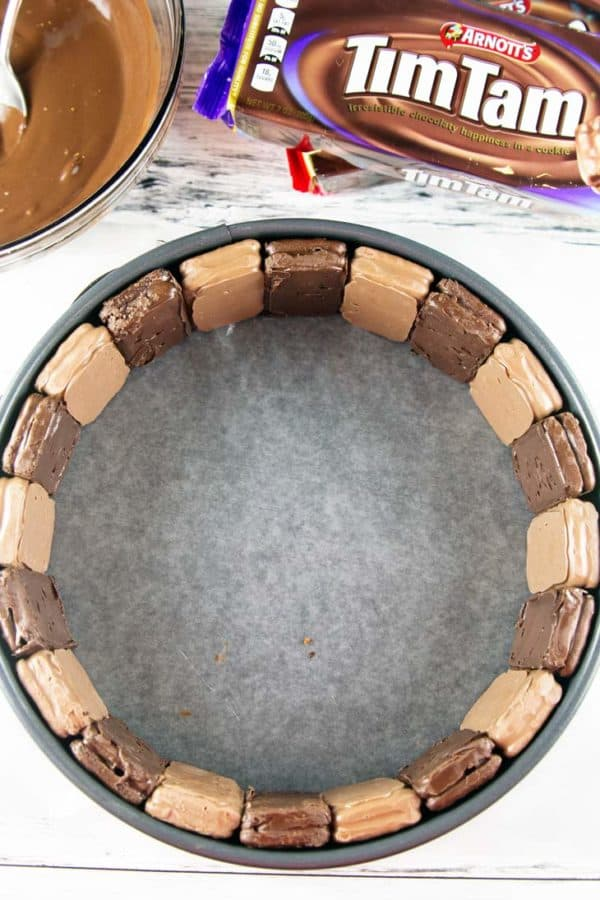 tim tams lined up along the outside edge of a springform pan