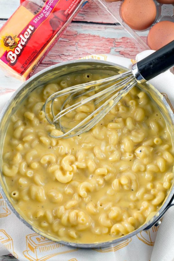 a large saucepan filled with creamy macaroni and cheese with a pale yellow cheesy sauce