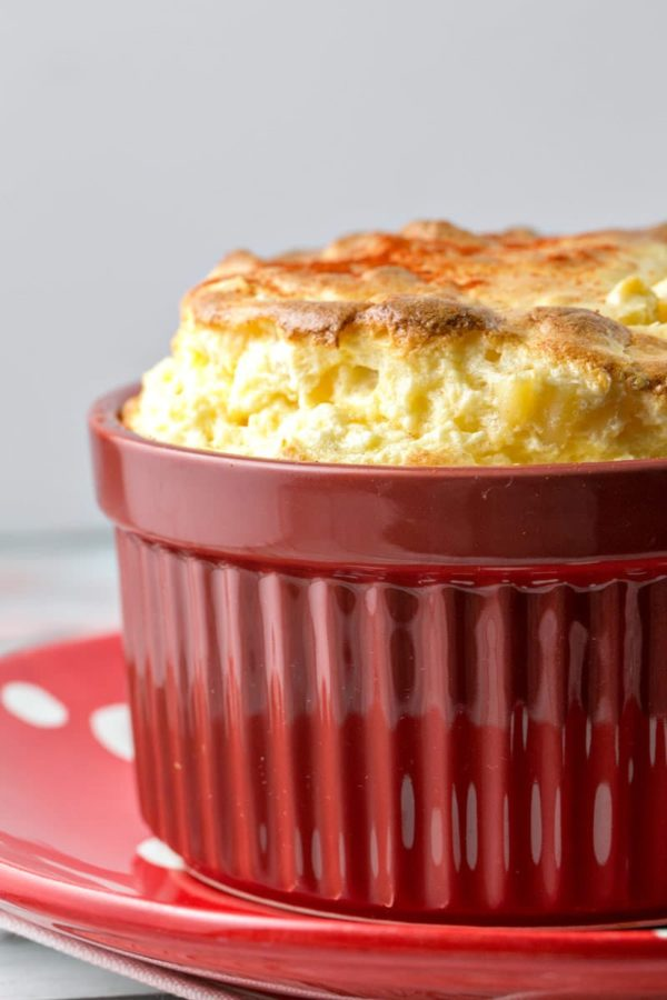 a towering souffle of cheese overtop macaroni and cheese in a red ramekin