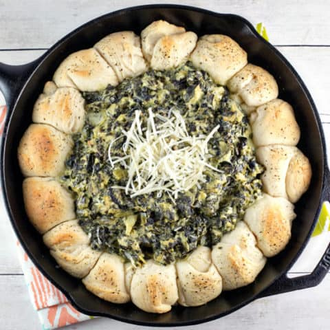 Up your spinach and artichoke dip game with this spinach and artichoke biscuit skillet - flaky biscuits surrounding bubbling hot dip! #bunsenburnerbakery #appetizers #dip #superbowl #partyfood