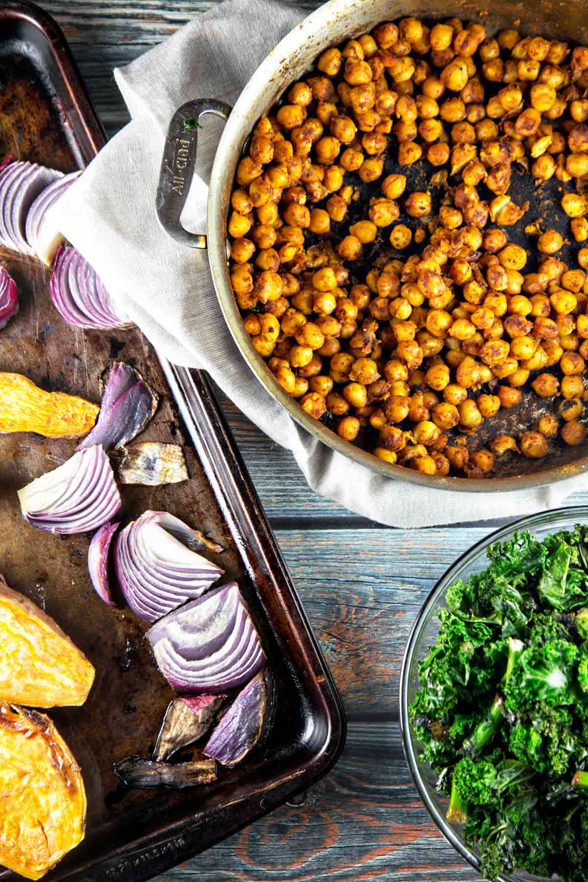 sheet pan with roasted sweet potatoes and onions next to a skillet with sauteed chickpeas and kale