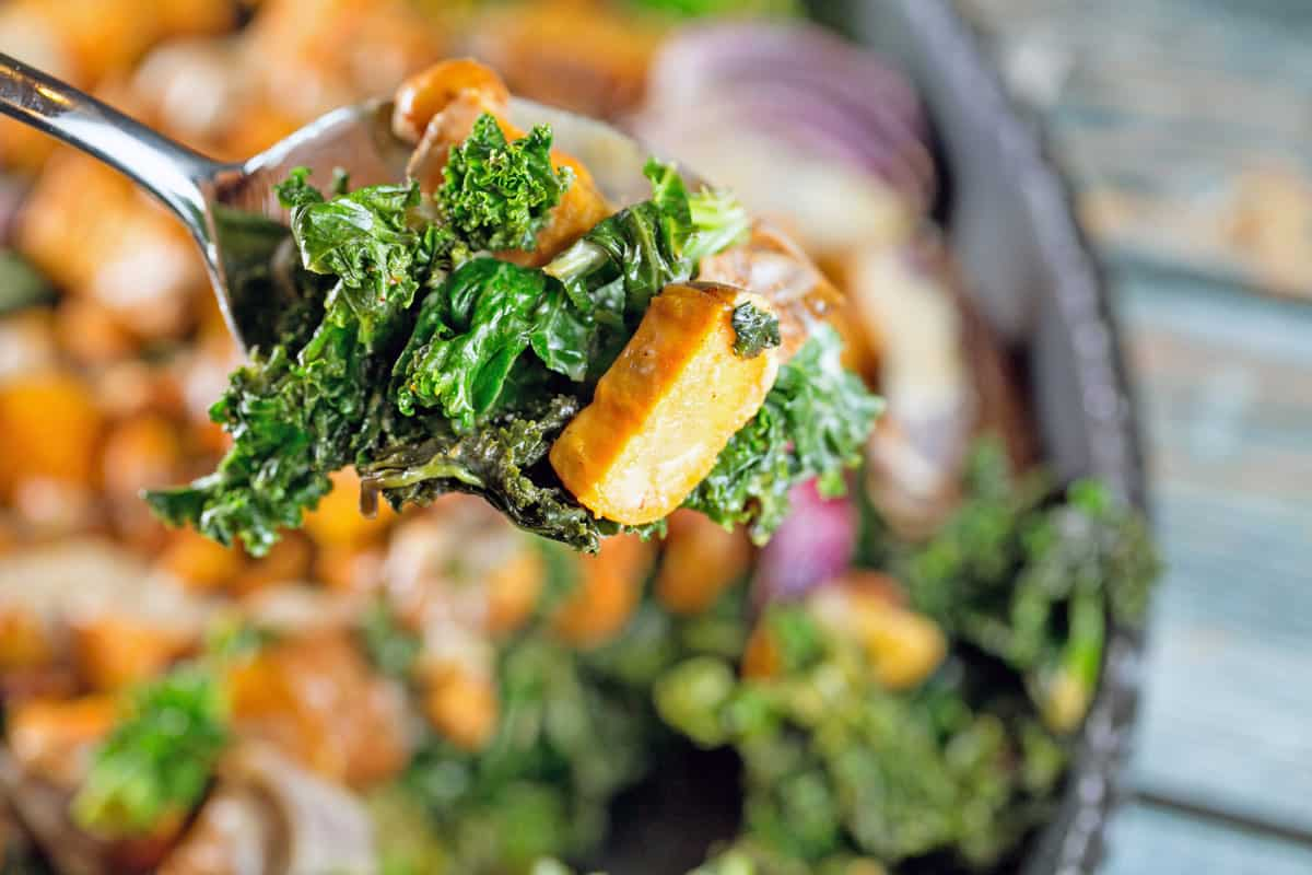 image of a fork holding a piece of kale and roasted sweet potato