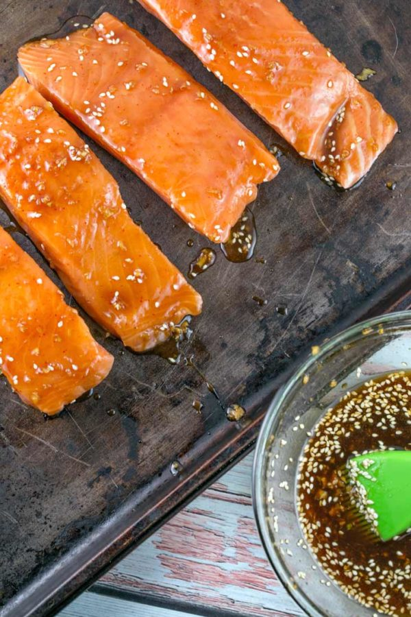 raw salmon getting brushed with a sesame asian sauce on a well worn sheet pan