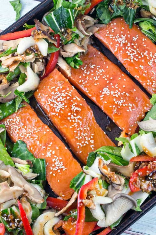 four raw bright pink salmon filets covered in an asian inspired sauce and topped with sesame seeds