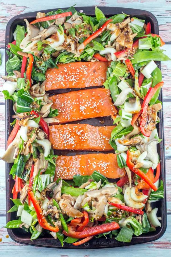 a sheet pan filled with vegetables and raw salmon covered in an asian-inspired sauce