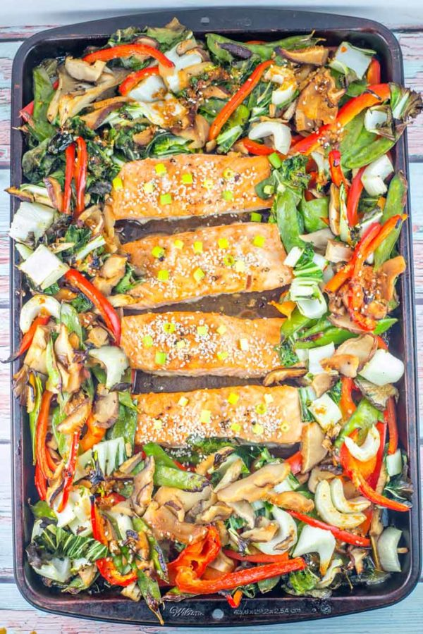 sheet pan full of cooked asian vegetables and four large salmon filets covered in an asian sauce