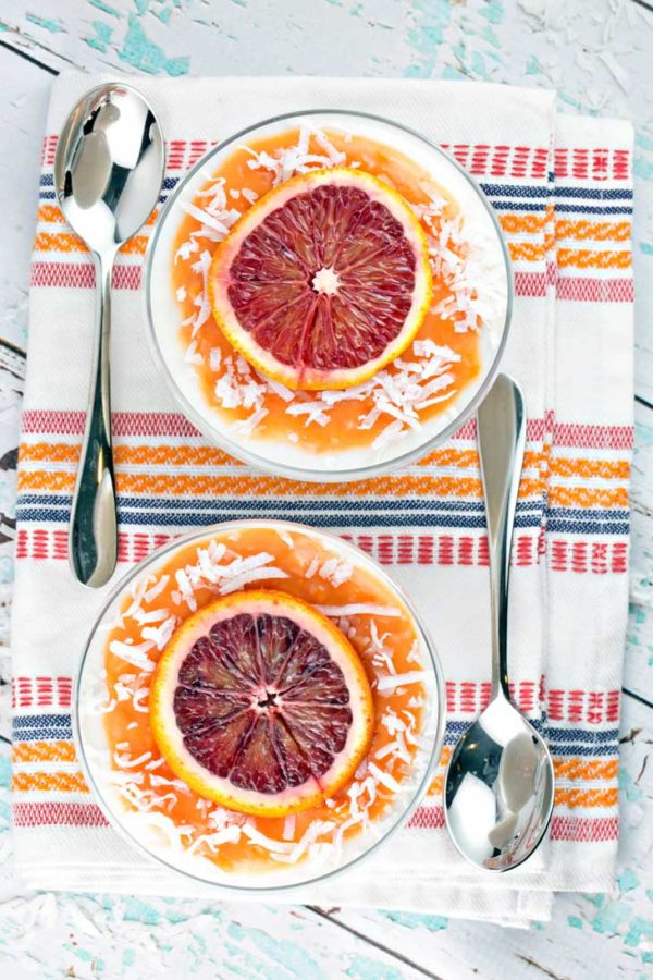Overhead view of two bowls full of coconut panna cotta topped with blood orange curd, blood orange slices, and shaved coconut on a colorful placemat with two spoons.