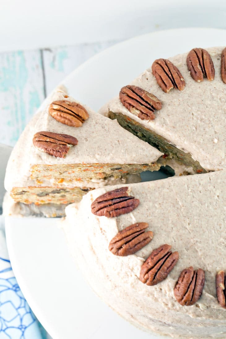 A slice of a moist two layer carrot cake covered with cinnamon cream cheese frosting decorated with pecans.