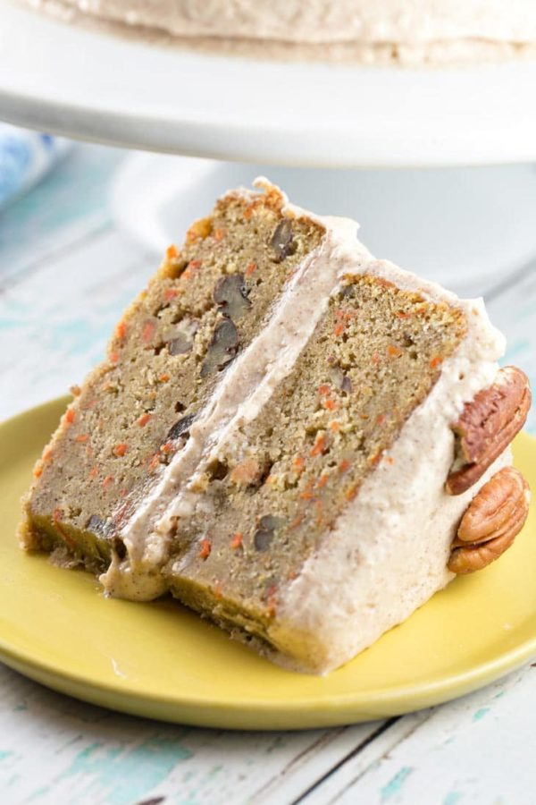 A single large slice of carrot cake covered with lemon cinnamon cream cheese frosting.