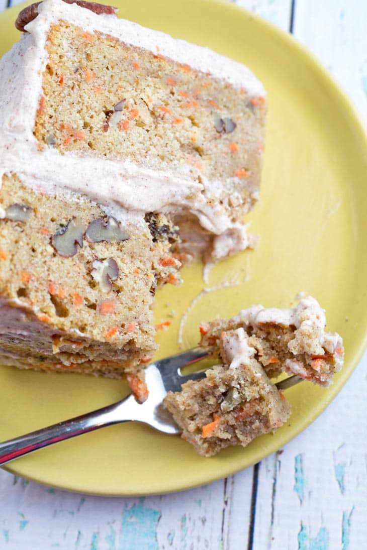 A single slice of carrot cake with lemon cinnamon cream cheese frosting with a forkful of cake.