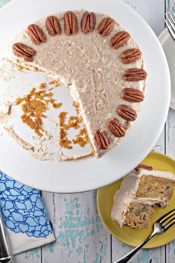 overhead view of a carrot cake with lemon cream cheese frosting with two large slices removed