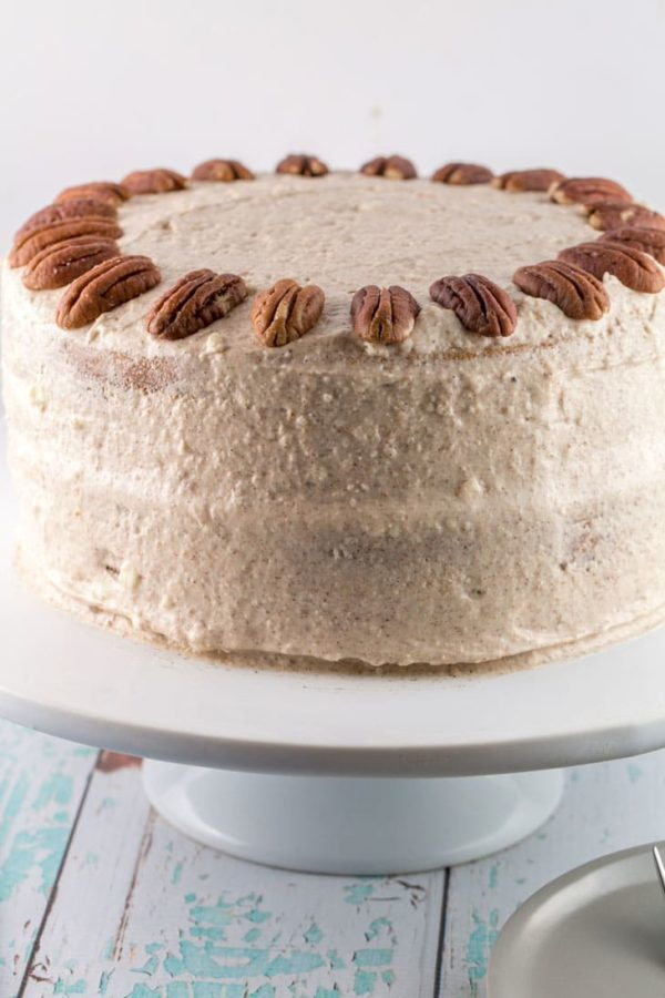 a two layer carrot cake covered in lemon cinnamon cream cheese frosting and pecans on a white cake stand