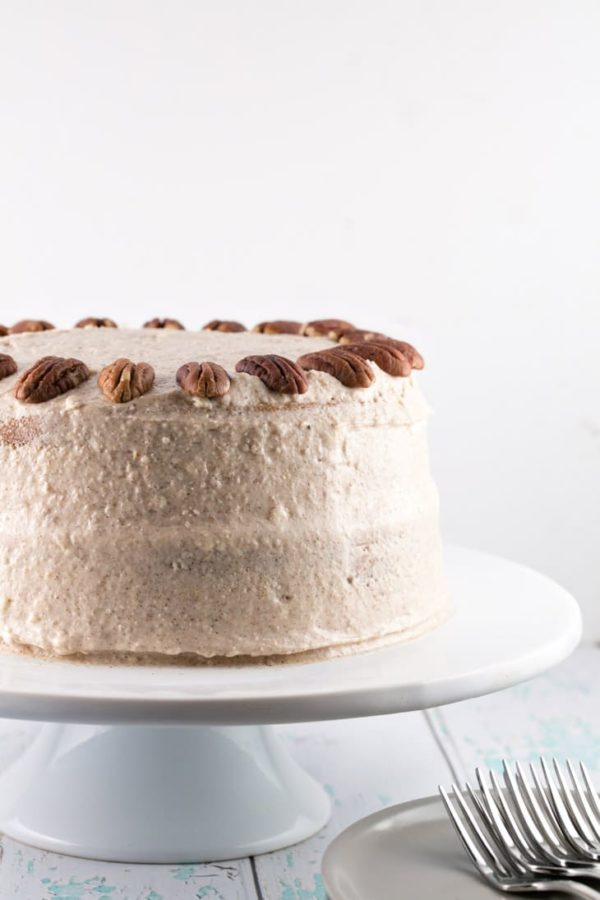 side view of a frosted two layer carrot cake with halved pecans decorating the top of the cake