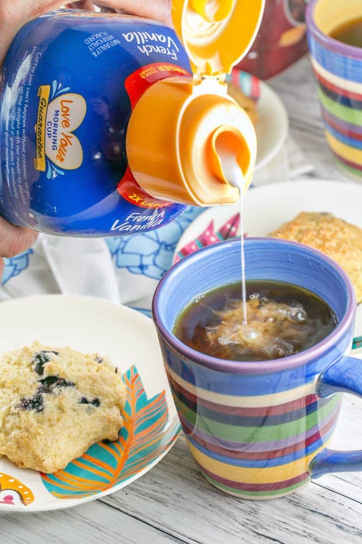 International Delight French Vanilla pouring into a cup of coffee with lemon blueberry scones.