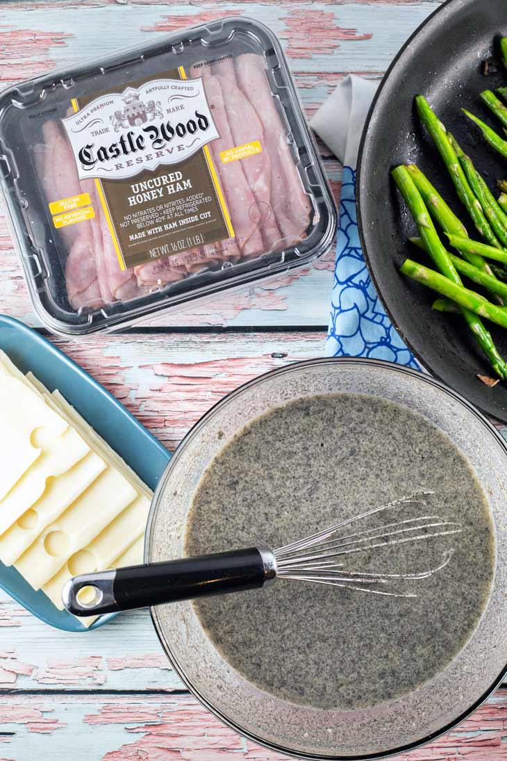 The necessary ingredients for ham asparagus crepe rolls: sliced ham, cheese, asparagus, buckwheat crepe batter.