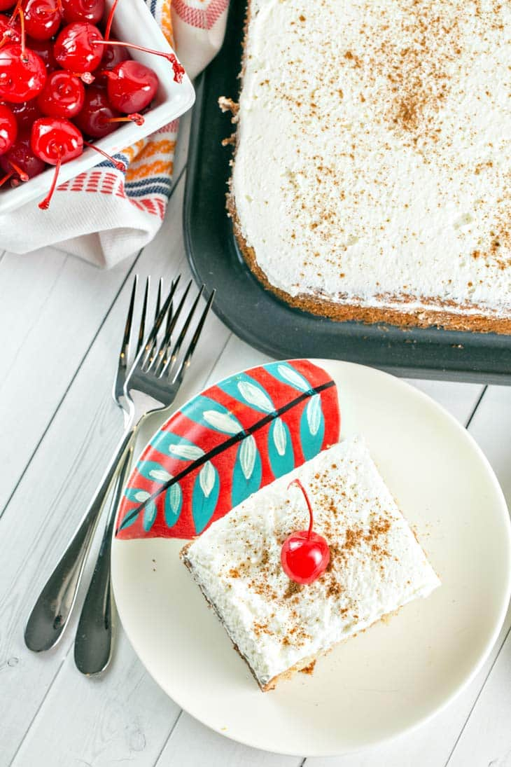 A slice of three milk soaked Tres Leches Cake with cinnamon and a cherry on top.