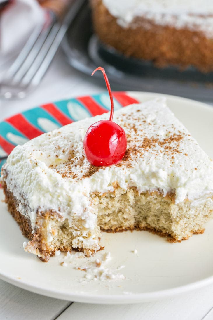 A few bites taken from a slice of Tres Leches Cake with a sprinkle of cinnamon and a cherry.