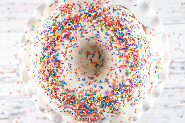 a funfetti bundt cake covered in opaque white frosting with a thick layer of rainbow sprinkles