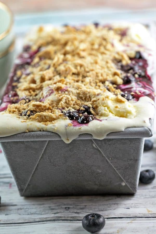 frozen blueberry pie ice cream layered in a loaf pan with vanilla ice cream, blueberry pie filling, and graham cracker crumbs