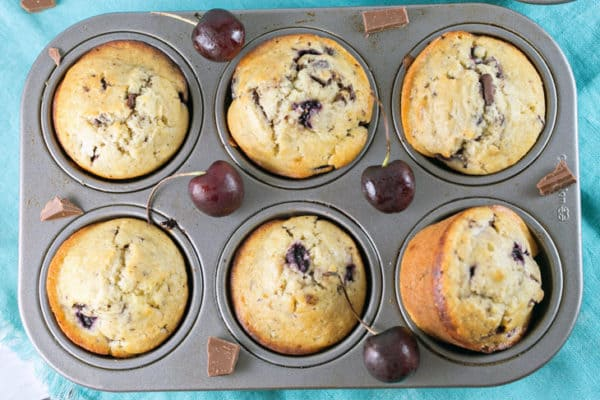 six cherry chocolate chunk muffins in a muffin tin surrounded by fresh cherries and chunks of chocolate