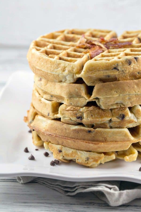 five bacon chocolate chip waffles stacked on a white plate
