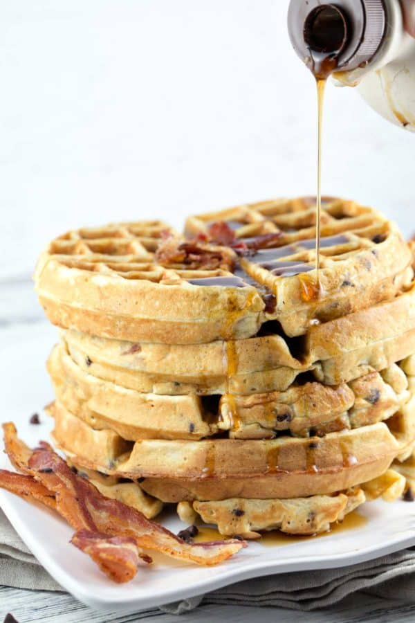 a stack of five bacon chocolate chip waffles with maple syrup poured on top