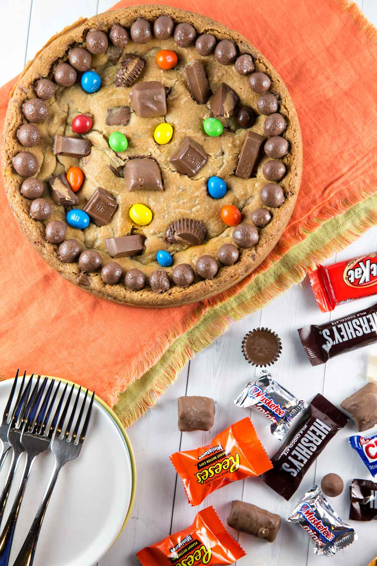 a cookie cake covered in candy on an orange placemat with candy wrappers scattered around