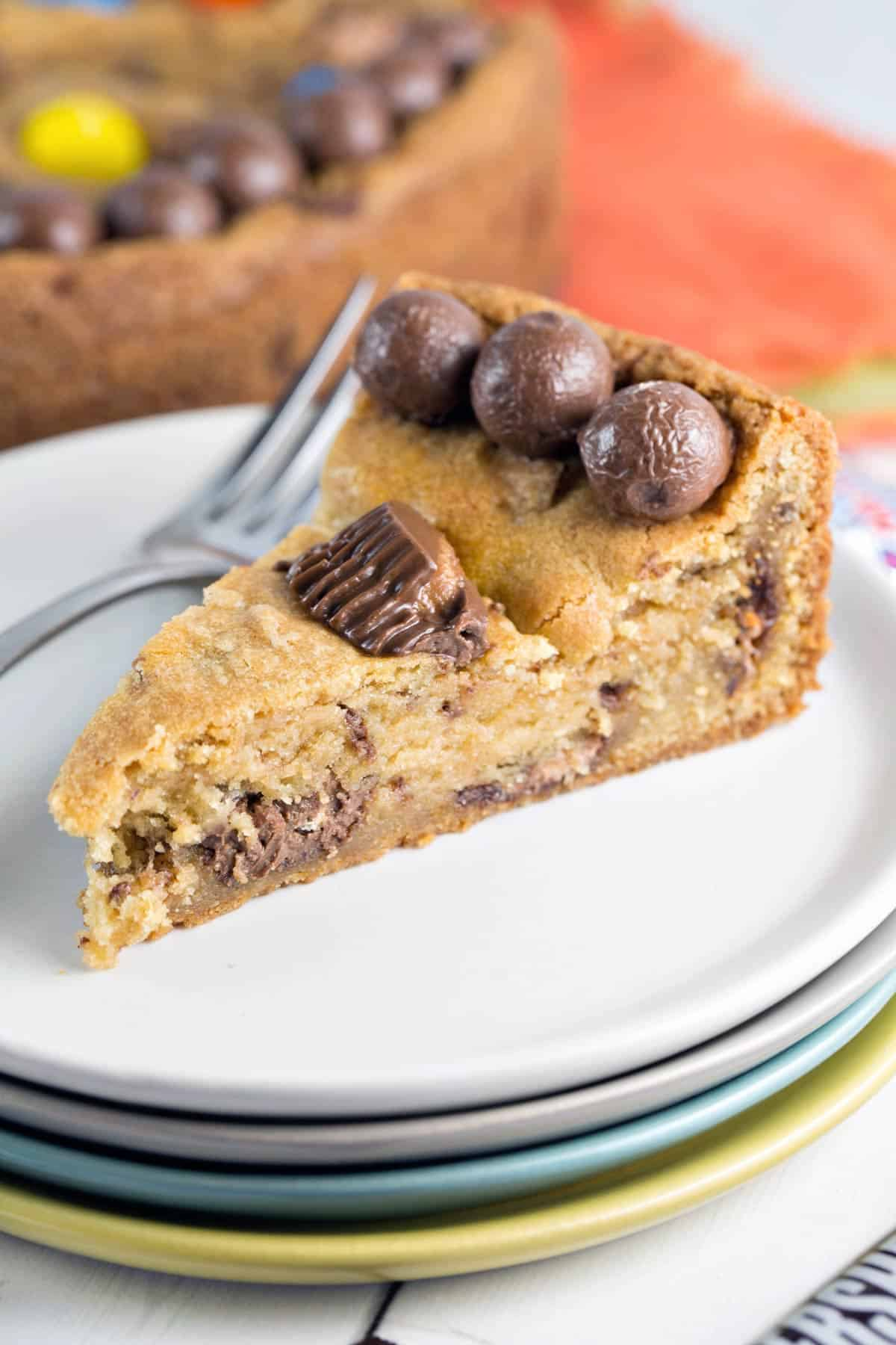side view of a slice of candy cookie cake showing the soft inside filled with candy