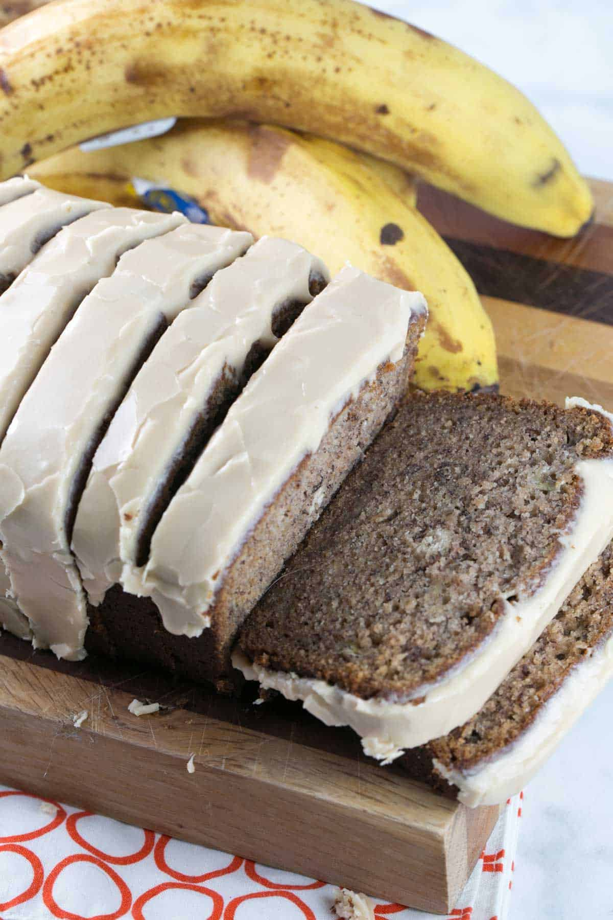 sliced maple glazed banana bread on a cutting board next to brown spotted bananas