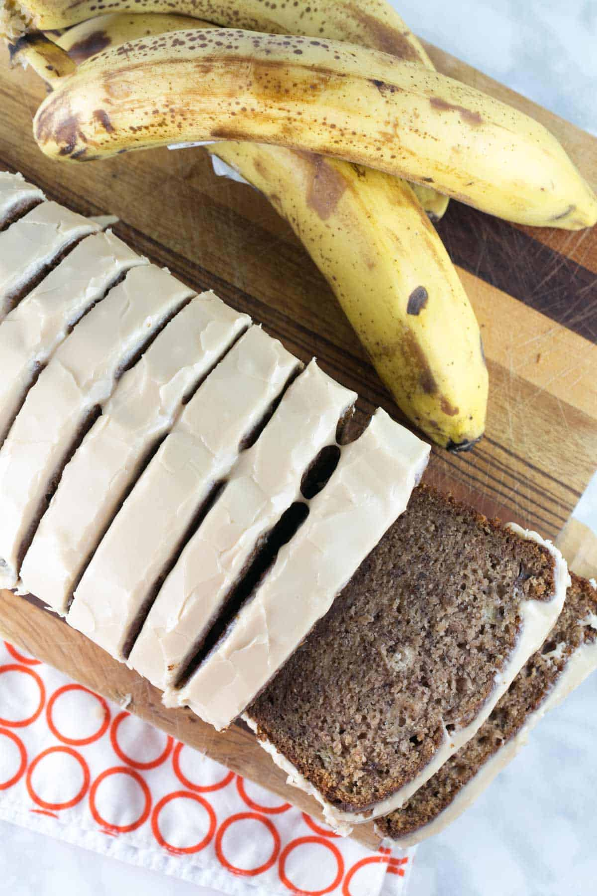 a loaf of maple glazed banana bread sliced on a wood cutting board