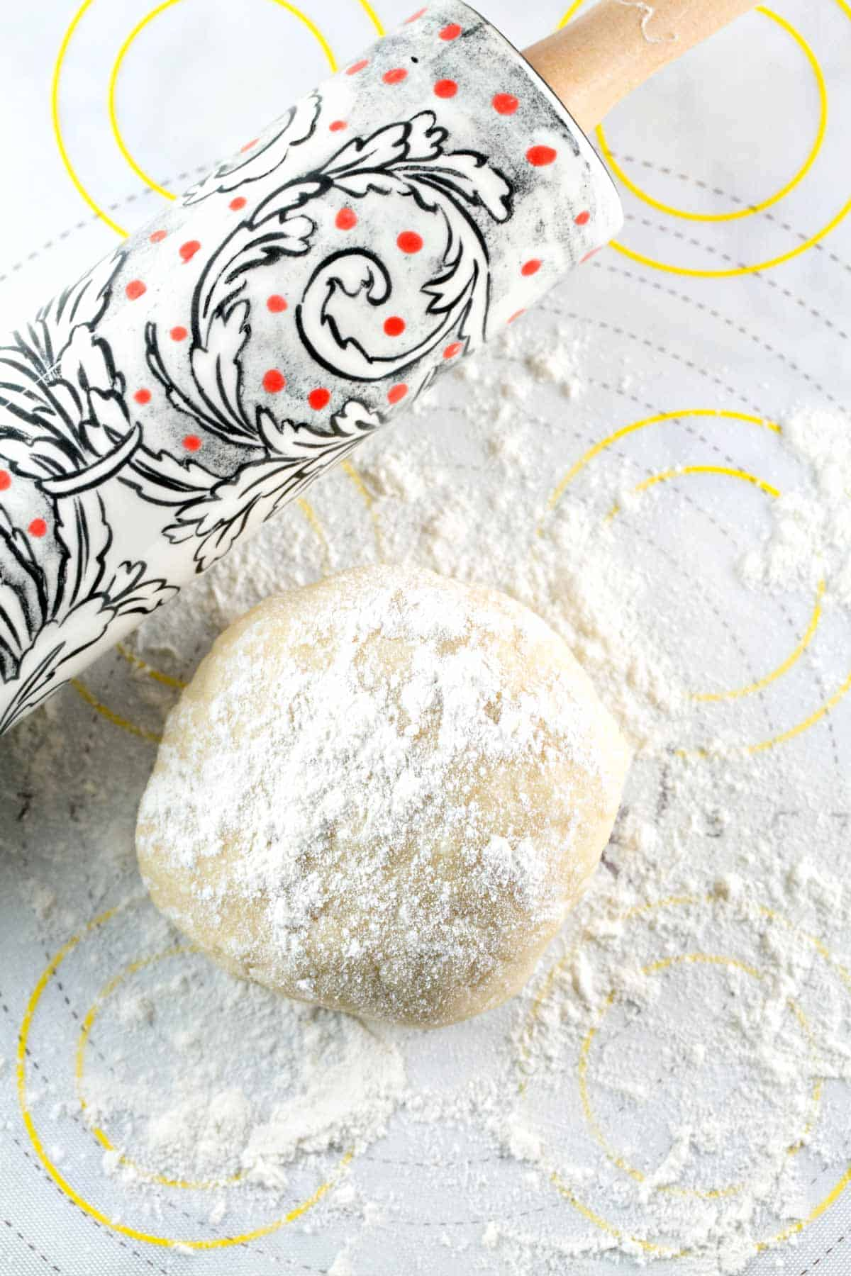 round ball of pie crust dough dusted with flour next to a decorative rolling pin