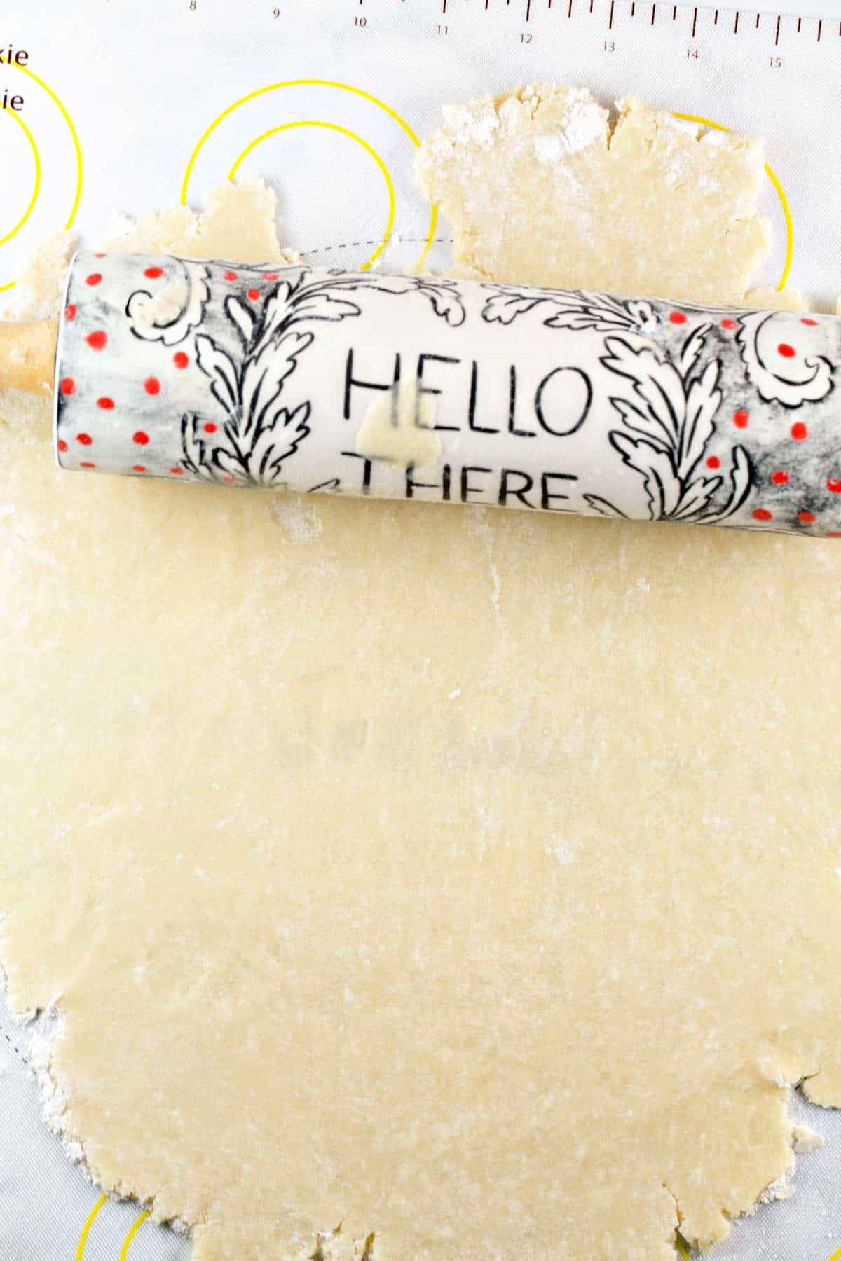 "pie crust dough rolled out in a flat sheet with a rolling pin with the words ""hello there"""