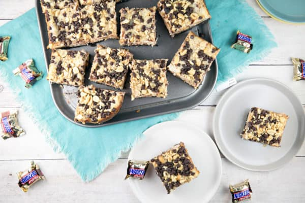 Snickers Cheesecake Bars: Handheld cheesecake bars full of chopped Snickers, a crunchy chocolate and peanut topping, and a drizzle of melted chocolate and caramel. #dessert #baking #cheesecake #Snickers #cheesecakebars {Bunsen Burner Bakery}