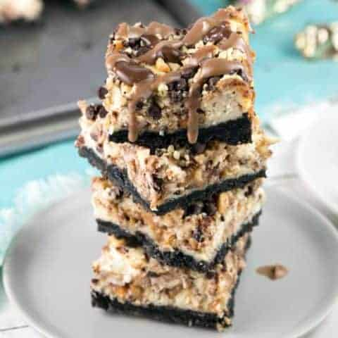Snickers Cheesecake Bars: Handheld cheesecake bars full of chopped Snickers, a crunchy chocolate and peanut topping, and a drizzle of melted chocolate and caramel. #bunsenburnerbakery #cheesecake #Snickers #cheesecakebars