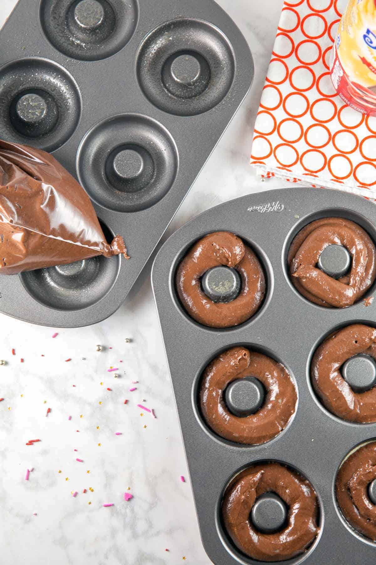 piping chocolate donut batter into a donut pan for baked peppermint mocha donuts